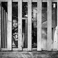 Young boy looking through the front porch balcony handrail of his home in the island of Bastimento, Bocas del Toro, Panama