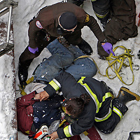 Rescuers tend to an unconscious man, who lays on the roof where he landed, after the crane he and a coworker were riding in tipped over on West St near Downtown Crossing. His partner died and this man received serious injuries.