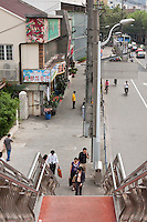 People climb up stairs on pedestrian bridge Shanghai China