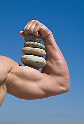 detail of muscular man's arm holding rocks against a blue sky