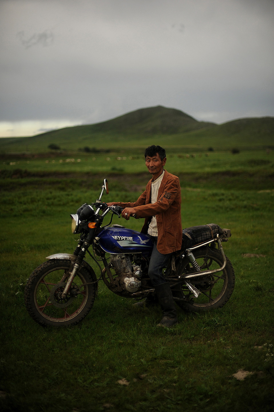 Mongolian herder Soninsaikhan sits on his motorcycle that he uses to get around the harsh terrain of the countryside. Mongolian herders are nomadic people usually moving place to place two to four times a year, depending on livestock's pasture. However the herders are moving less these days, which is causing over grazing leading to desertification. — © Jeremy Lock/USAF
