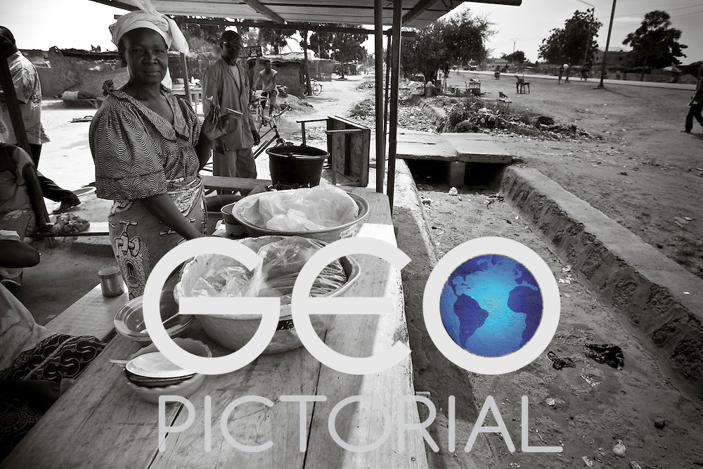 A food stall by an open sewage gutter in shanty suburb of Ouagadougou.
