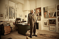 Philanthropist and businessman Denis Adam photographed in his office. At his shoulder is a portrait of his wife, Verna Adam.