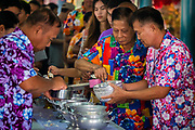 Members of the congregation fill rice bowls that will be presented to the monks on the first day of Songkran in rural Nakhon Nayok, Thailand. PHOTO BY LEE CRAKER