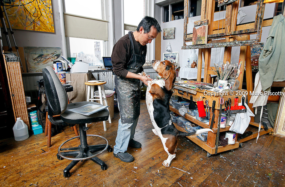 SHOT 12/22/09 2:03:26 PM - Artist Quang Ho, 46, of Littleton, Co. painting in his studio at the Art Students League of Denver space. Ho specializes in everything from still lifes to landscapes to figures and started drawing as early as age four. He is often kept company while he works by his two basset hounds 'Putter' (pictured), a three year old male, and 'Birdie' (not pictured), a one and half year old female. (Photo by Marc Piscotty / © 2009)