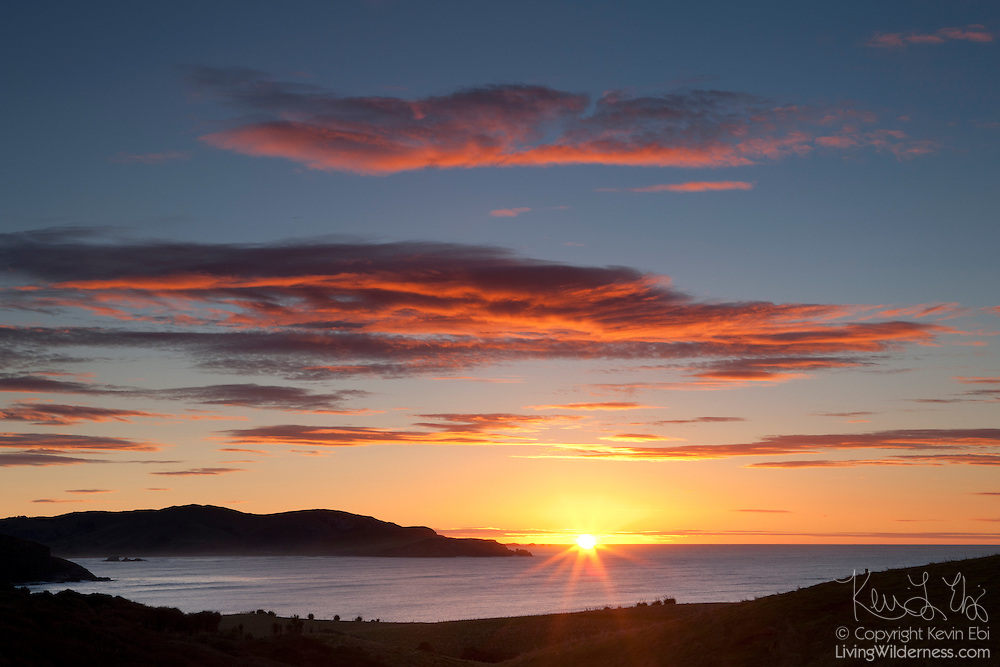 The sun rises over the Catlins Heads near Owaka in southeastern New Zealand.