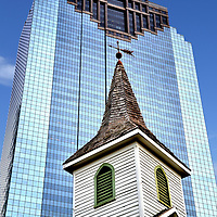 St. John Church Steeple and Heritage Plaza Building in Houston, Texas <br /> During the 1970s and early 1980s, the race was on in Houston, Texas, to build numerous skyscrapers. Soon the horizon became the third tallest skyline in the U.S. This construction surge ended in the mid-80s with a recession, a decline in real estate values, an oil industry collapse and the savings and loan crisis. The last major project during the boom was the Heritage Plaza. The high-rise stands 762 foot and has 53 floors. In stark contrast is the modest St. John Church. It was built about one hundred years earlier in 1891. The landmark is located in Sam Houston Park along with other historical buildings. This public greenspace provides a quiet, western view of downtown.