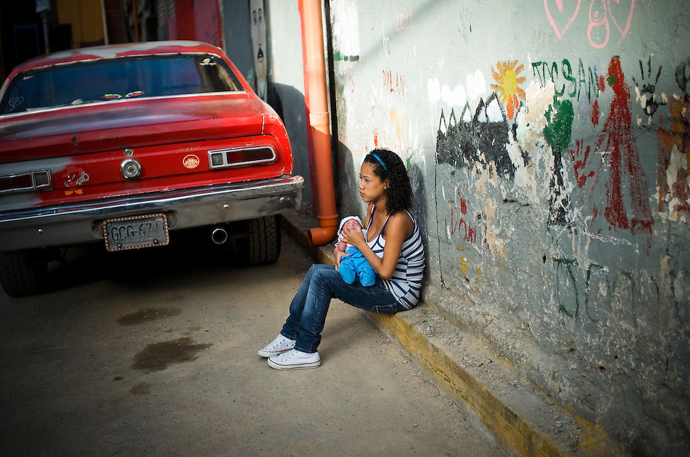 15-year-old Yanaifre Acevedo, sits in the street with her newborn baby, Dilan, in a slum in Caracas, Venezuela. Acevedo, who wants to be a professional dancer, said she got pregnant by accident, but that she has a secret plan to have her aunt watch her baby so that she can go back to school. She also plans to get a job so that she and her boyfriend can move into their own apartment together. She says her boyfriend is excited to be a father, but he has hardly visited her and their son.