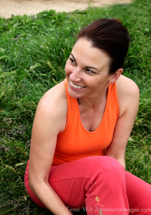 USA, California. Healthy natural woman, mid-30's to 40's, in exercise clothing outdoors, smiling.