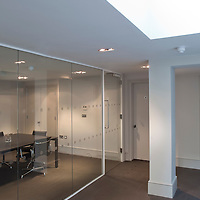 Modern office interior, meeting room behind glass windows with roof light.