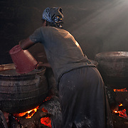 A woman preparing large cauldrons of pito, an alcoholic beverage made from millet, in Agbogbloshie, a slum in Ghana's capital, Accra. The work is extremely hot, and the acrid smoke burns the eyes and lungs.