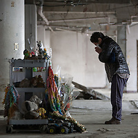 A woman prays at a shrine with offerings of flowers and incense, at the entrance to the Minami-Sanriku Hospital, on the 1 year anniversary of the March 11th 2011 earthquake and tsunami, in Minami-Sanriku, Tohoku region, Japan on Sunday 11th March 2012.