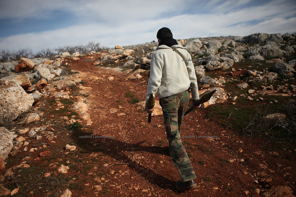 A FSA soldier carry RPG. On 22. February the syrian army attacked the village of Kureen, Province of Idlib, Syria. Kureen was among the first villages in the northwest of Syria controlled by the opposition. Some villagers and members of the defence units escaped to surrounding olive orchards, when the attack begun in the early morning. A majority of the inhabitants didn´t manage to escape. The heavy shelling lasts 7 houres. Soldiers searched all houses, burnt some of them down, loote shops, stole cars and furniture. About 60 motorcycles were burnt down. Tanks demolished several houses. 6 men were executed. One woman died as a result of an heart attack.