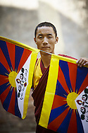 A Tibetan Buddhist monk prepares to hang Tibetan flags in McLeodGanj, Dharamsala, India.