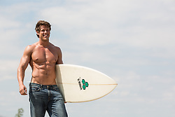 shirtless muscular man with a surfboard