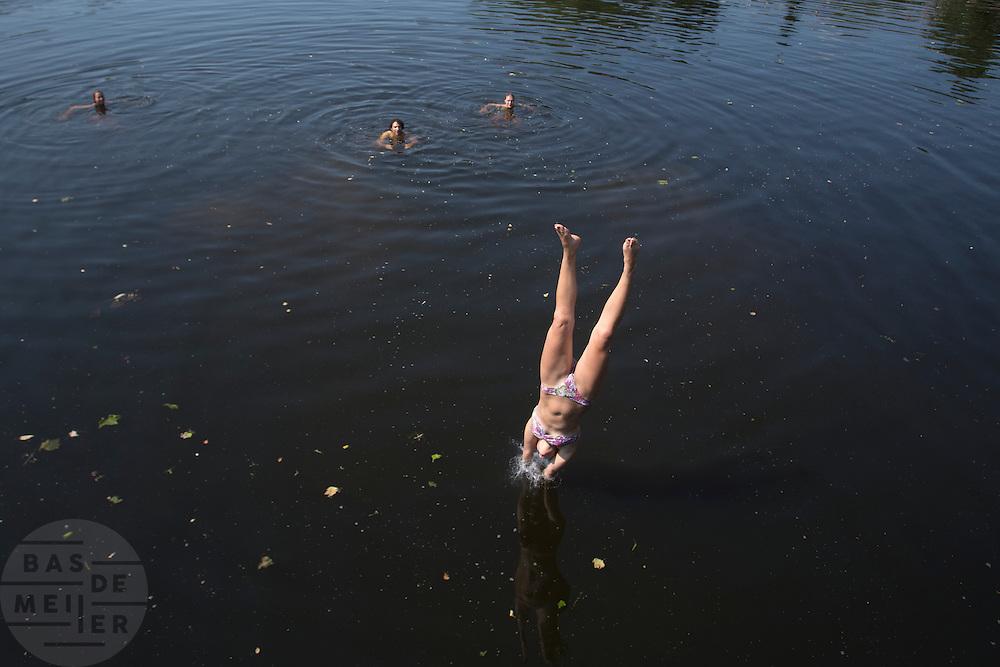 Een meisje duikt vanaf de Muntbrug in Utrecht het verkoelende water van het Merwedekanaal in. Op waarschijnlijk de laatste mooie zomerse dag genieten mensen nog volop van de zon.<br /> <br /> Young people are jumping of a bridge in Utrecht into the cool water of the Merwedekanaal.