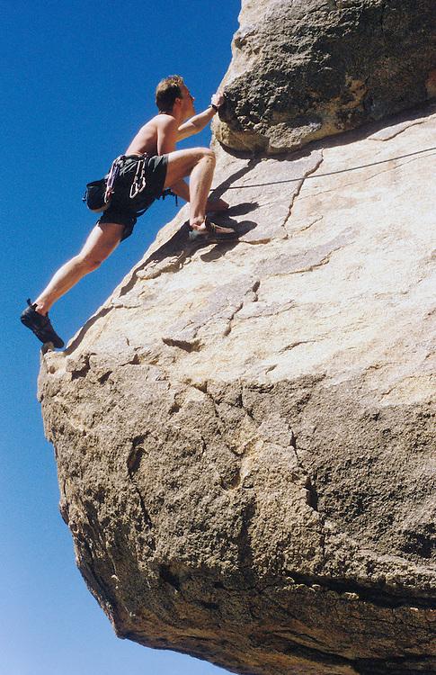 Late 20's Caucasian man rock climbing.  Joshua Tree national Park, California, USA.  Headstone Rock.<br />