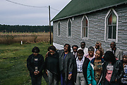 Members of the New Revival Methodist Church in Madison, Md pray outside during the sunrise service on Easter morning. The historic church is now threatened by sea level rise, and the older members aren't sure it will survive much past their lifetime.