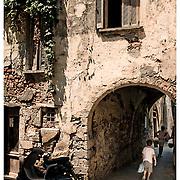 Children walking through archway below Venetian period house in Chania, Crete, Greece.