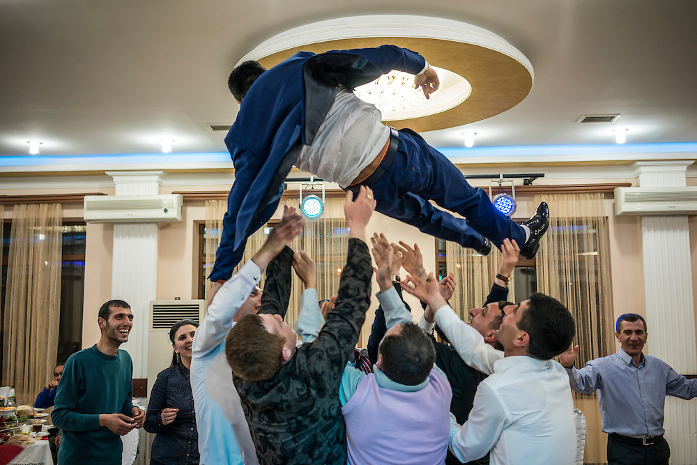 STEPANAKERT, NAGORNO-KARABAKH - APRIL 18: Groom Davit Simonyan, 24, is tossed into the air by friends and family at his wedding reception on April 18, 2015 in Stepanakert, Nagorno-Karabakh. Since signing a ceasefire in a war with Azerbaijan in 1994, Nagorno-Karabakh, officially part of Azerbaijan, has functioned as a self-declared independent republic and de facto part of Armenia, with hostilities along the line of contact between Nagorno-Karabakh and Azerbaijan occasionally flaring up and causing casualties. (Photo by Brendan Hoffman/Getty Images) *** Local Caption *** Davit Simonyan