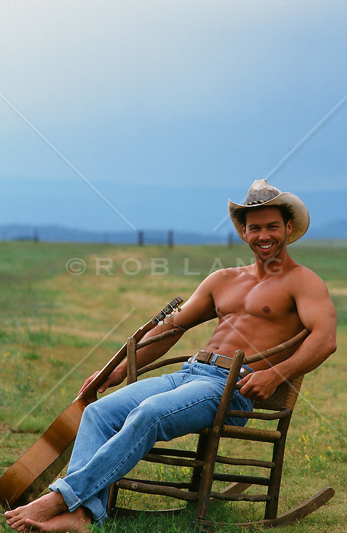 shirtless cowboy in a chair on a ranch rob lang images