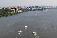 New York, New York - Three personal watercraft head south on the Hudson River toward Manhattan on a summer afternoon in a view from the George Washington Bridge on July  11, 2015. The New York City skyline is visible in the background.
