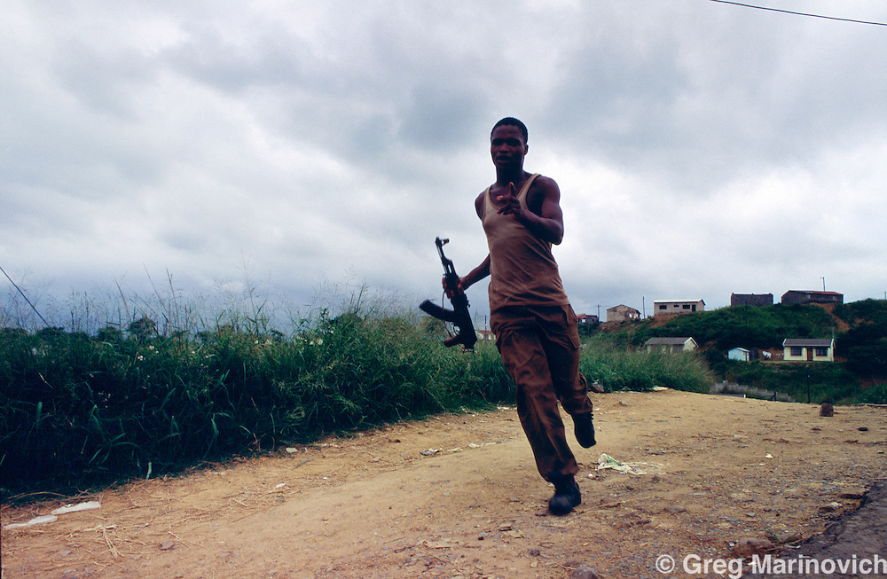 Umlazi township, KwaZulu Natal, South Africa, 1995: A Inkatha Freedom Party supporter runs with a AK47 during a march in Umlazi township south of Durban. 1995.