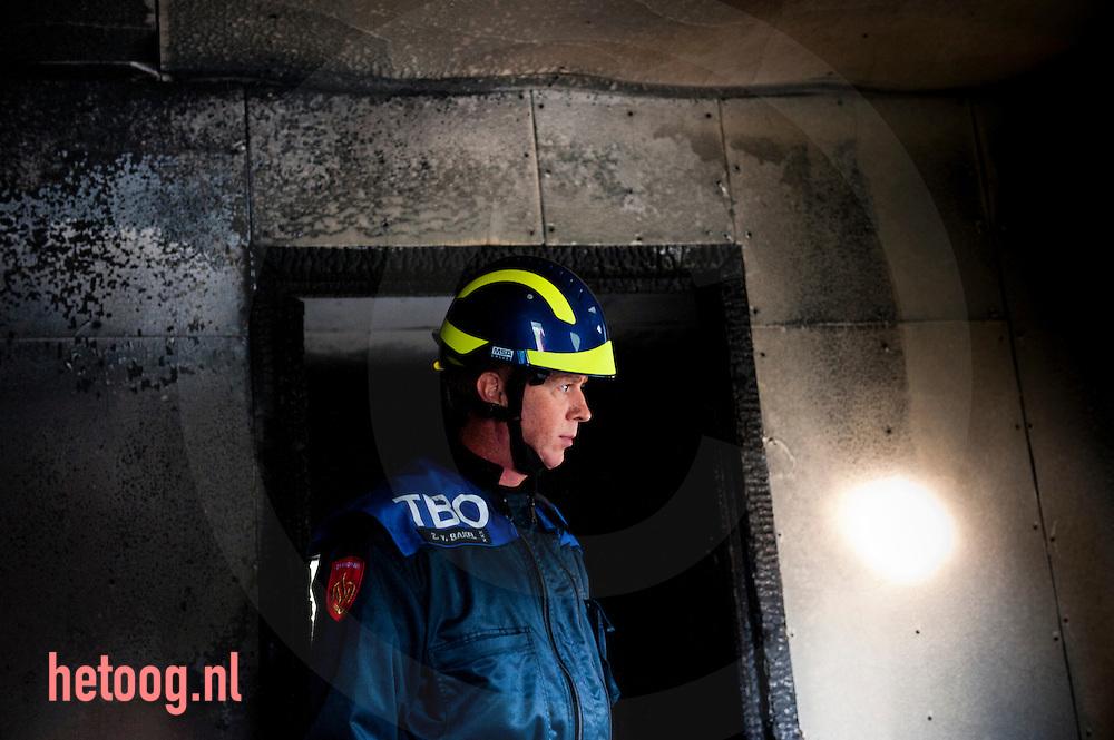 Nederland, enschede, 05okt2011 brandonderzoekers (van de brandweer,politie ,technischerecherche, etc.) tijdens een cursus op zoek naar de oorzaken van een brand. Op het voormalige militaire vliegveld twenthe worden brandonderzoekers getraind in het analyseren van het ontstaan en verloop van branden