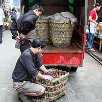 Asia, China, Chongqing. Local delivery of greens in street market in the city of Chongqing.
