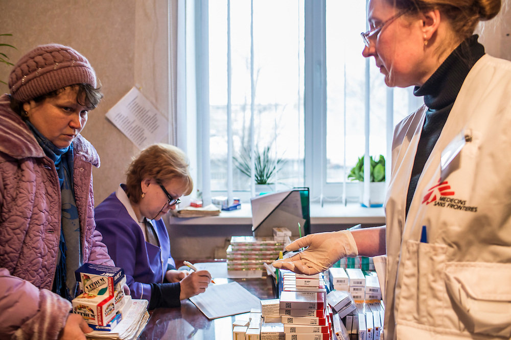 ZIMOGORYE, UKRAINE - MARCH 15, 2015: Venera Lukyanchenko, center, a general practitioner at the Zimogoryivskaya Ambulatory, and Lidia Grishko, a physician with Medecins Sans Frontieres, right, consult with a patient in Zimogorye, Ukraine. CREDIT: Brendan Hoffman for The New York Times