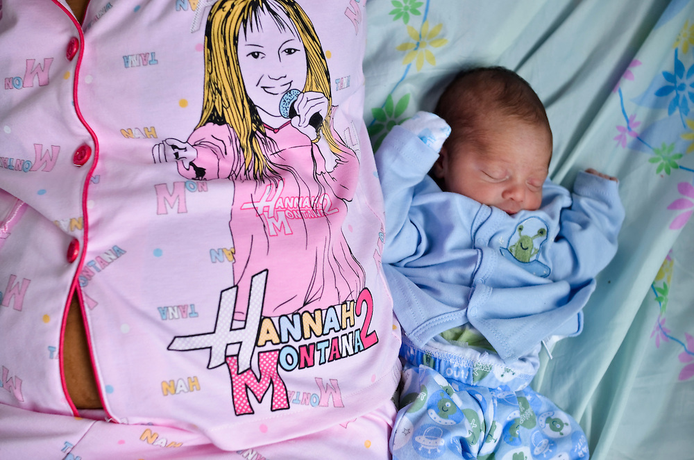 15-year-old, Yanaifre Acevedo, dressed in Disney's Hannah Montana pajamas, rests next to her baby Dilan at a free, government-run maternity clinic in Caracas, Venezuela.  Acevedo, who wants to be a professional dancer, said she got pregnant by accident, but that she has a secret plan to have her aunt watch her baby so that she can go back to school. She also plans to get a job so that she and her boyfriend can move into their own apartment together. She says her boyfriend is excited to be a father, but he has hardly visited her and their newborn baby.