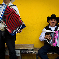 A pair of mariachis pass the time on Cesar Chavez Boulevard in East Los Angeles playing their music. Please contact Todd Bigelow directly with your licensing requests.