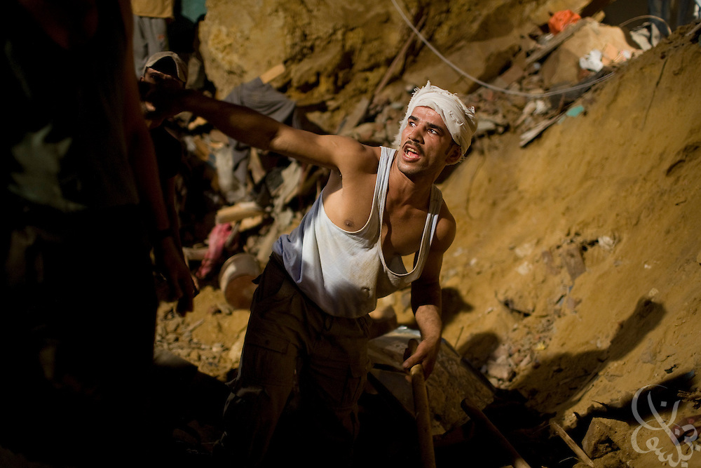 Egyptian residents of the Manshiyet Nasr shantytown frantically dig by hand to reach trapped relatives following a rock slide that killed at least 64 and buried perhaps hundreds more Saturday September 06, 2008 on the eastern edge of Cairo, Egypt. Residents have complained that the government appears to be doing little to reach possible survivors, and have clashed with police at the site of the disaster.