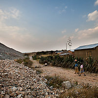 Villager walk between discarded waste rock from the North Mara mine and the houses of people who have refused to leave their homes in Nayagota on July 31, 2010.