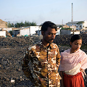 Local residents look at the waste dumped in their village by steel rolling factories.