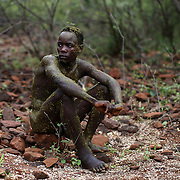 A young Pokot man sits on stones after having been smeared by elders with the contents of the stomach of a bull during an initiation ceremony to become recognised as an adult within his community, about 80 Kilometres from the town of Marigat, in Baringo County, Kenya, January 20, 2016.