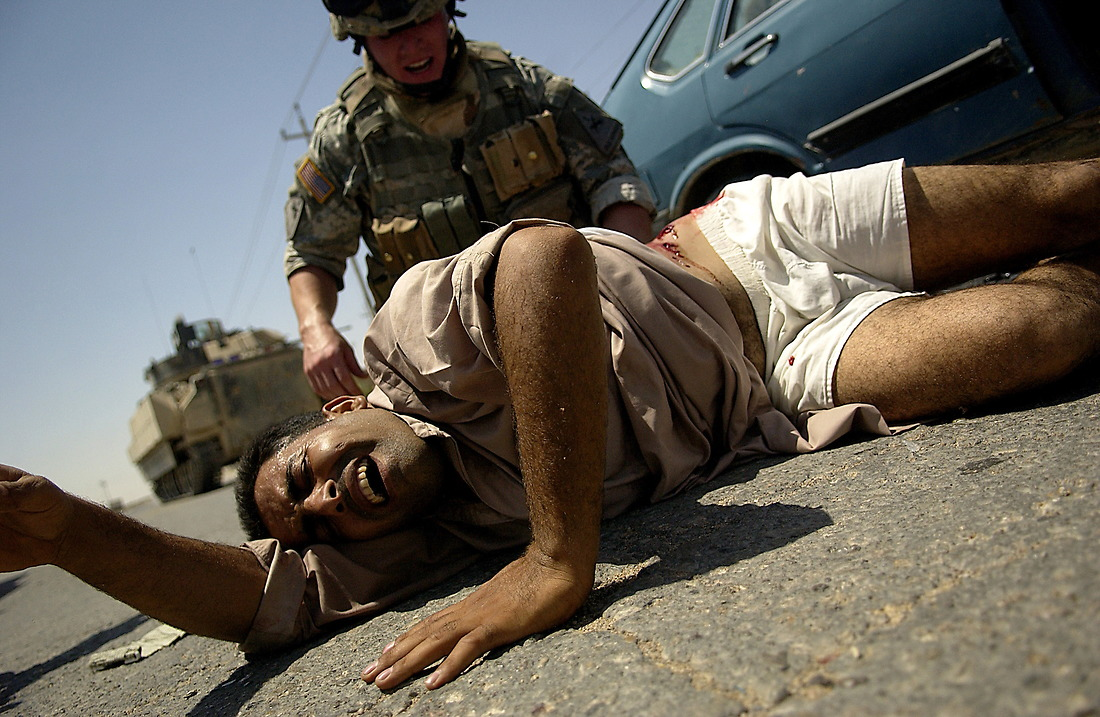 CPL David Stigers from Bravo Company, 2nd Battalion, 6th Infantry Regiment, 1st Armored Division, Baumholder, Germany, administers first aid to an injured Iraqi man that was shot on August 16, 2006. U.S. Forces came under fire from anti-Iraqi Forces during a Traffic Control Point (TCP) on Alternate Supply Route Michigan in Tameem, Ramadi, Iraq.  TCP's are performed by pulling over random vehicles and searching the vehicle and it's occupants for weapons or explosives being transported into the city. — © TSgt Jeremy Lock/