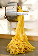 Fresh home-made pasta tagliatelle coming out of pasta machine