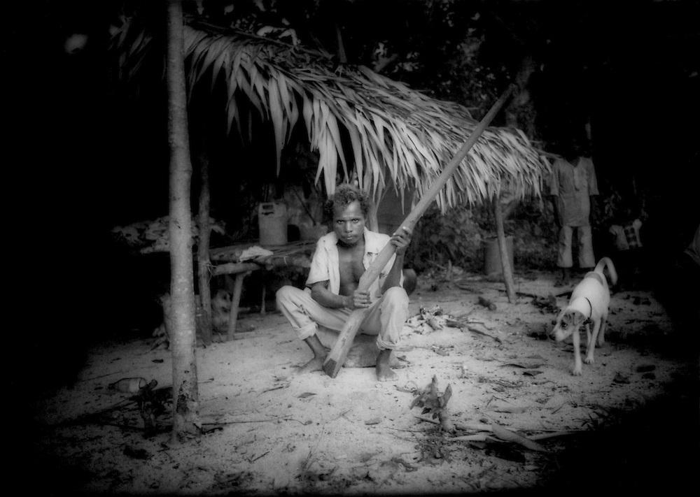 Dumagat Negrito man with speargun at his hut, Palaui Island, Philippines.