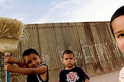 Children play next to the US-Mexico border fence in Mexicali, Mexico on Thursday, April 13, 2006.<br />