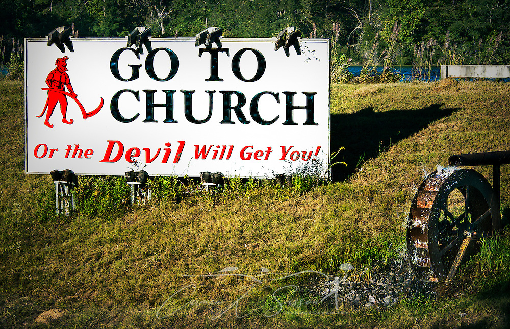 """A roadside sign warns drivers along Alabama Highway I-65 North in Deatsville that they need to to church the avoid the wrath of the Devil. The sign was erected by the late W.S. """"Billy"""" Newell in the late 1980's as a way to """"wake up the people,"""" Newell told NPR in 2005. Newell briefly changed the sign to, """"We Love Lucy,"""" when 2006 gubernatorial candidate Lucy Baxley. Newell died in 2009. (Photo by Carmen K. Sisson/Cloudybright)"""