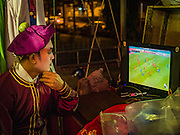 08 DECEMBER 2016 - BANGKOK, THAILAND:  A cast member watches a soccer game between Thailand and Myanmar before going on stage at a Chinese opera (also called ngiew in Thailand) performance at Pek Leng Keng Shrine in the Khlong Toei neighborhood of Bangkok. Public performances of music and celebration were banned during the first 30 days of the mourning period for Bhumibol Adulyadej, the Late King of Thailand. Now, nearly two months after the revered monarch's death, Bangkok street life is returning to normal and Chinese temples and shrines are once again scheduling operas.     PHOTO BY JACK KURTZ