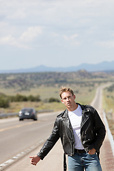 man in a leather jacket hitchhiking on a road in New Mexico