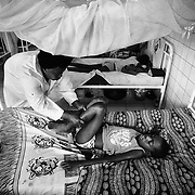 Deo Gracia Bomda, 12, who suffers from palsy following a polio infection, lies in bed while being massaged by a health worker at the Tie-Tie hospital in Pointe-Noire, Republic of Congo, on Thursday December 2, 2010.