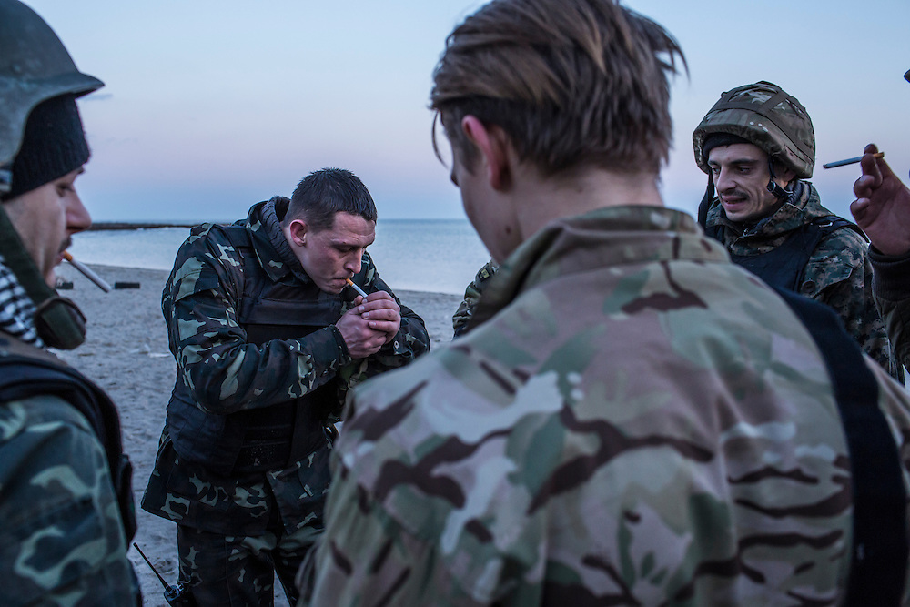 MARIUPOL, UKRAINE - FEBRUARY 4, 2015: New recruits of the St. Mary's Battalion take a cigarette break after a training exercise on the beach at their base on the Sea of Azov in Mariupol, Ukraine. The pro-Ukraine battalion is one of a few tasked with defending the port city, which was hit late last month by an artillery barrage that killed at least 30 people, from pro-Russia rebels. CREDIT: Brendan Hoffman for The New York Times