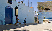 Four children playing in front of an old house In the town of Zefat, Israel. This blue painted house was owned by Rabbi Shmuel Abu, who came to Zefat in 1817 from Algiers with his three sons, Avraham, Yitzhak and Ya'akov. In addition to being a Rabbi he was also a real estate broker.