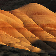 Low-angle sunlight shows the texture of the colorful Painted Hills in the John Day National Monument in Oregon. The layers represent different ash and pumice deposits from the Cascades and area volcanoes. The deposits were laid down approximately 33 million years ago. The red comes from rusty iron minerals; golden layers are rich with oxidized magnesium and iron, metamorphic claystone; the black comes from manganese.