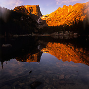 Mountains' red glow reflects in Dream Lake, winter, Rocky Mountain NP, CO.