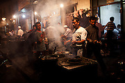 Kashgar: Uighur men prepare traditional Uighur food such as mutton kebabs, boiled goats heads and breads...Despite the migration of millions of Han Chinese to the western part of the Xinjiang Uighur Autonomous Region, the Uighur community continue to practice their muslim culture and resist the suppression of their cultural and religious traditions by the Chinese government....The chinese government has been criticised for the redevelopment of the old city, which has involved the destruction of many of the old houses in the town that were built without regulation, officials claiming them to be overcrowded and uncompliant with earthquake codes...Many in the chinese government believe Kashgar to a breeding ground for Uighur separatists, who Beijing claim to have links to terrorism...The european parliament has called for a halt to the cultural destruction of Kashgar, suggesting that Kashgar be added tot he UNESCO World heritage 'Silk Road' project, and calling on the chinese government to develop a genuine Han-Uighur dialogue to adopt more inclusive and comprehensive economic policies in Xinjiang in order to protect the cultural identity of the Uighur population..©JTanner/July 2011