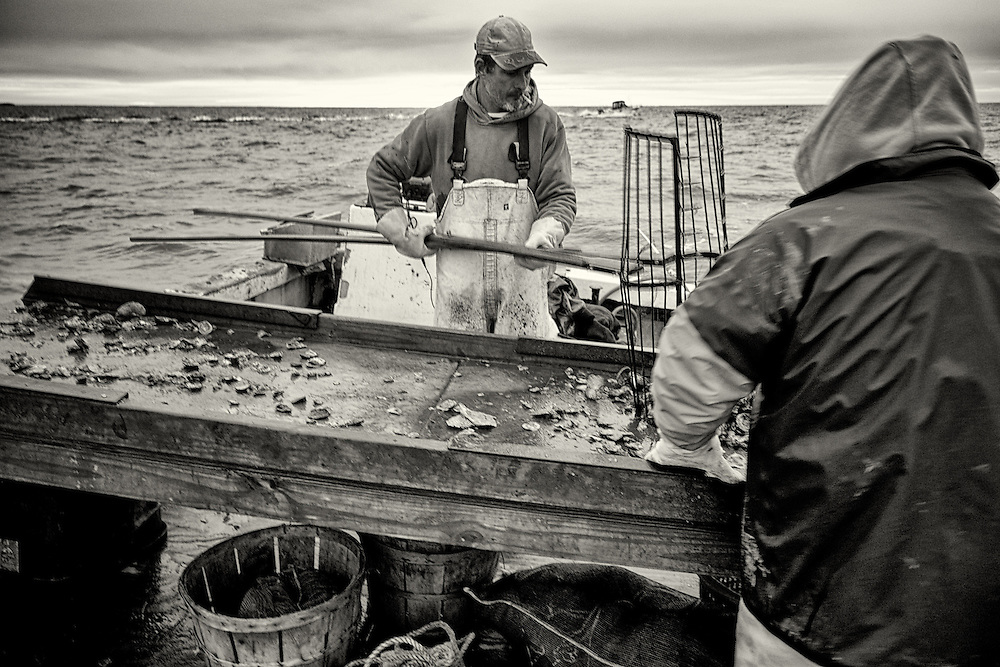 Joe Lawson and his helper fill the 4th bushel. In the winter, water on the floor of the boat usually freezes. This was a good day for Joe; after 9 hours in the Bay, 14 oyster bushels were full.<br />